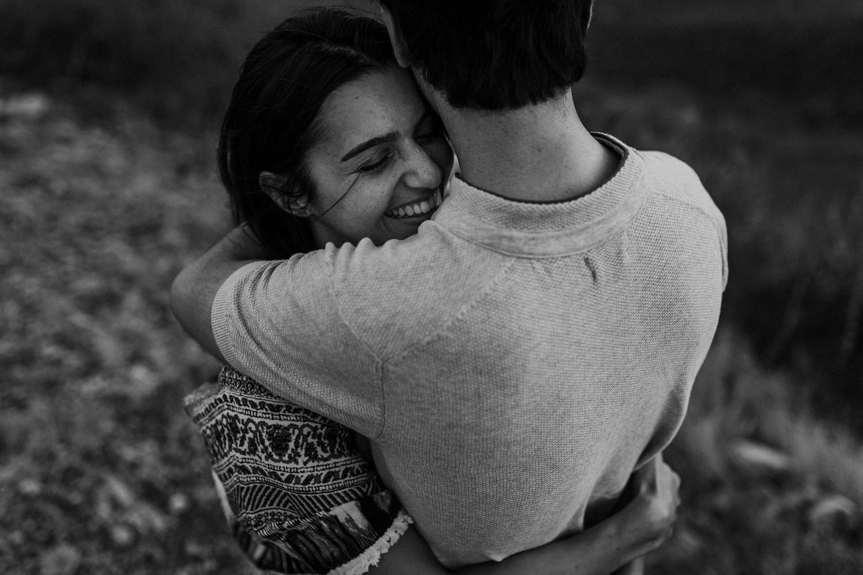 rapariga sorri enquanto abraça o namorado numa fotografia a preto e branco