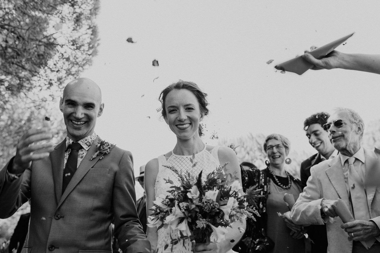 noivos a sorrir enquanto convidados lançam pétalas