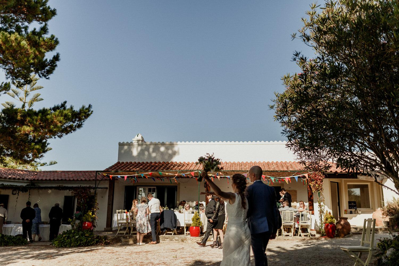 ramo da noiva no ar enquanto casal se dirige para os seus convidados