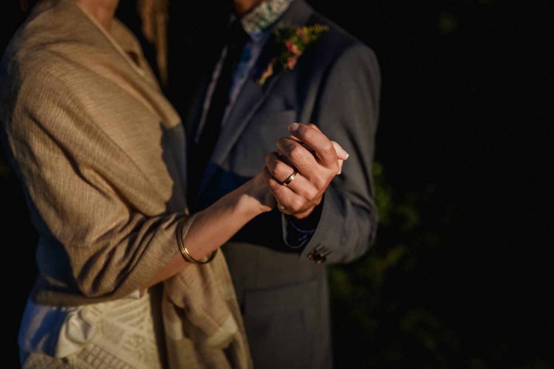 noivos de mãos dadas a mostrar a aliança