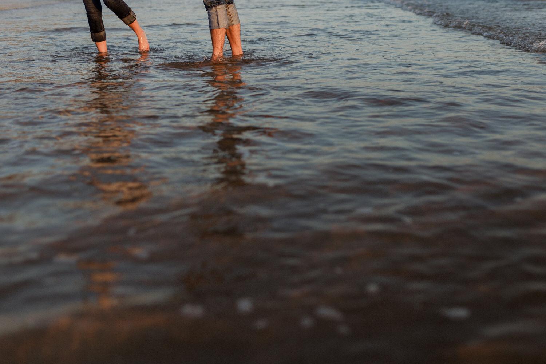 pernas de um casal a andar na água da praia da fonte da telha