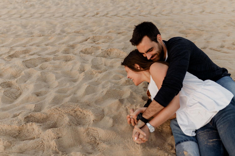 noivos rebolam na areia em brincadeira para sessão de noivado
