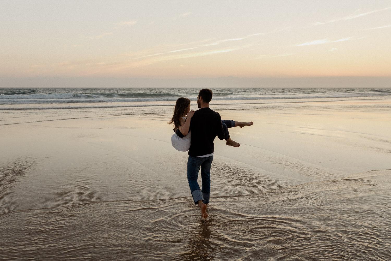 namorado carrega namorada nos braços pela água da praia da fonte da telha