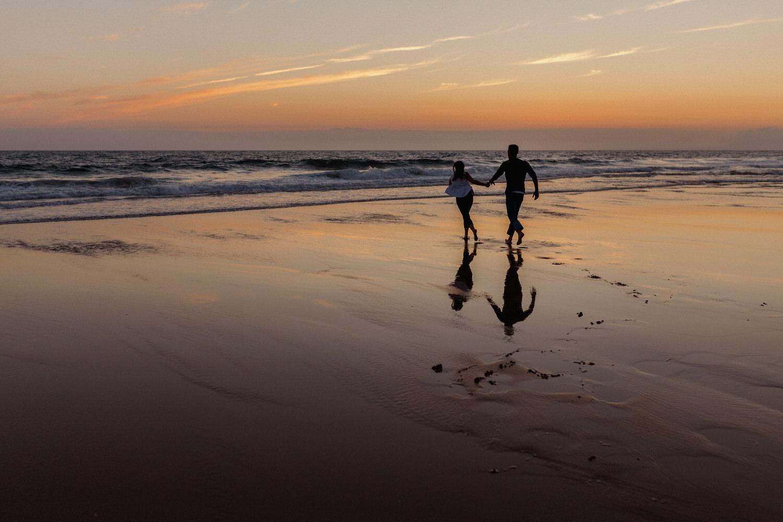 namorados a correr ao por do sol em sessão na praia da fonte da telha