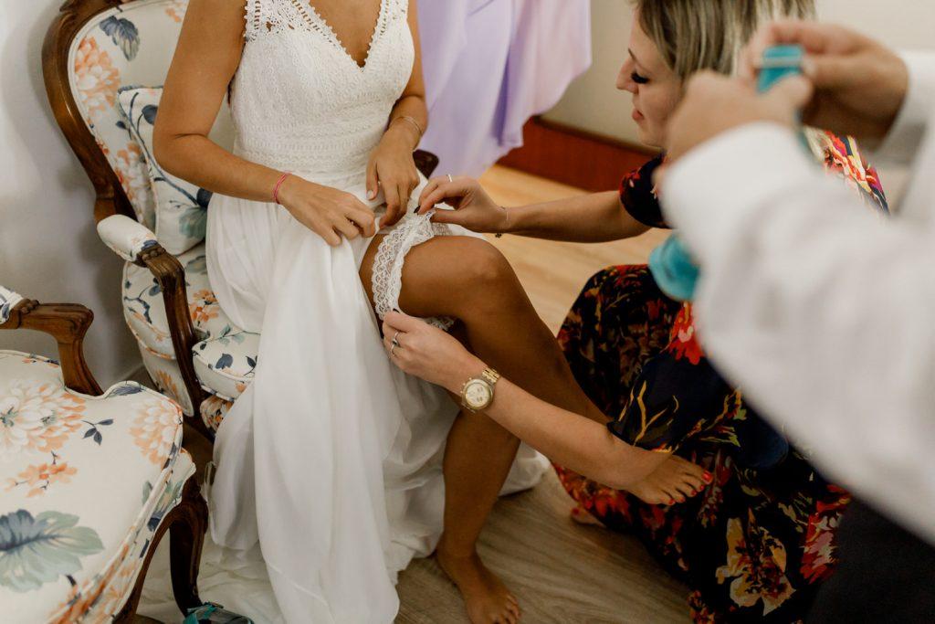 maquilhadora a colocar a liga na perna da noiva