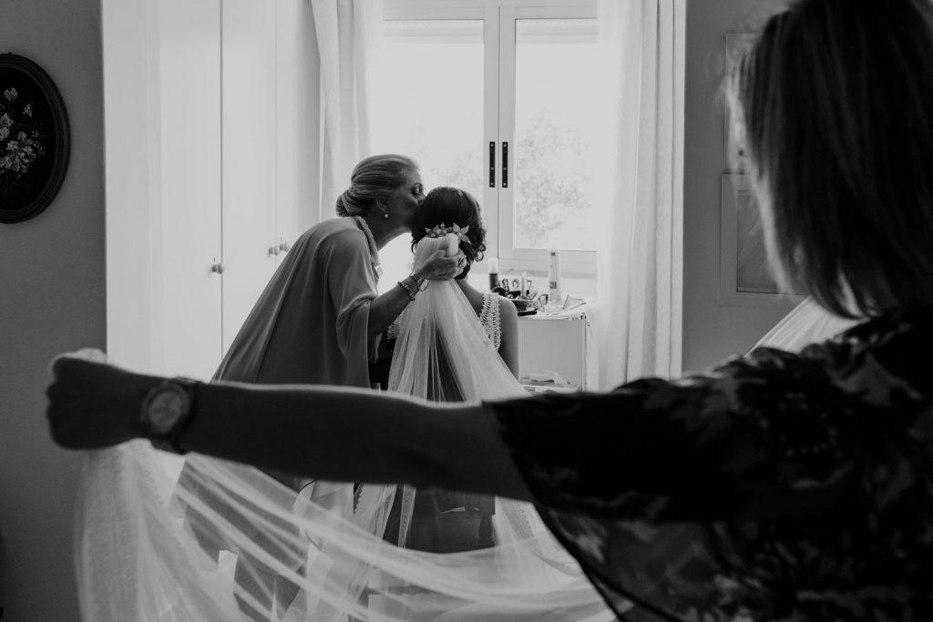 mãe da noiva a dar um beijo enquanto coloca o véu