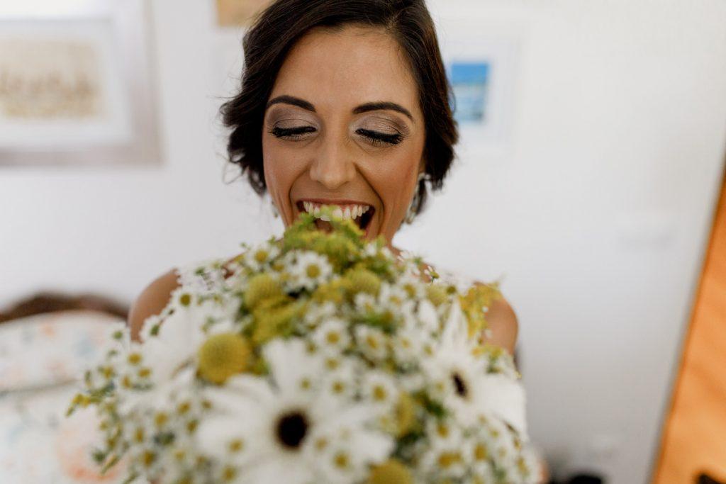 noivo sorri enquanto mostra o bouquet em almada