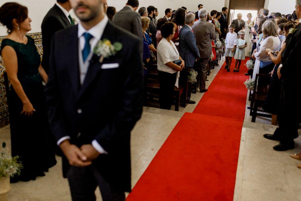 noivo espera pela noiva enquanto ela caminha até ao começo da cerimónia de casamento