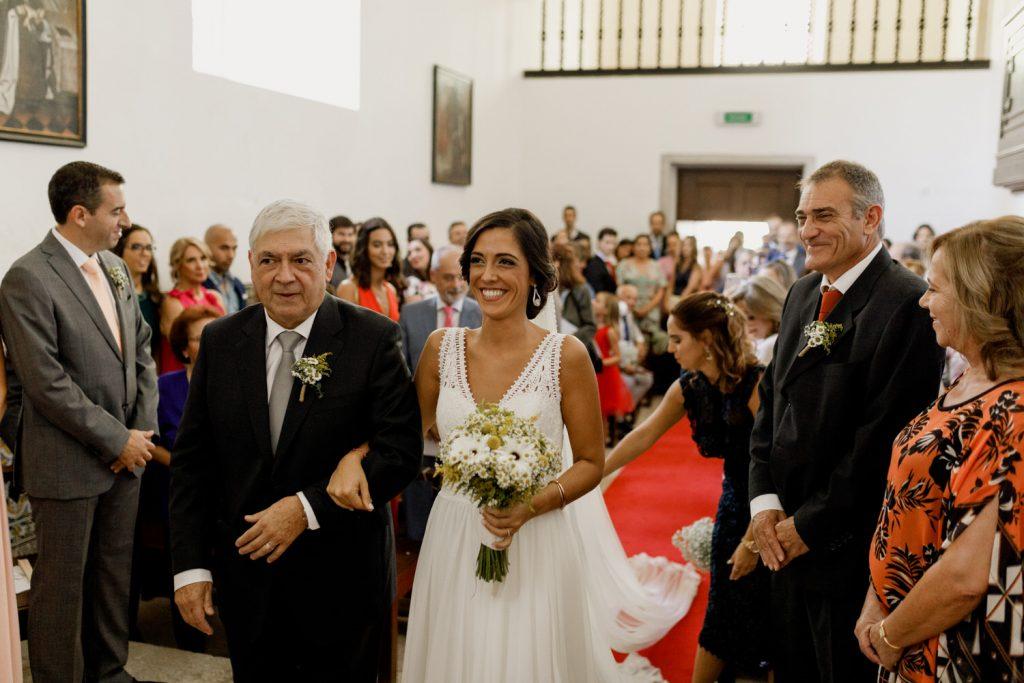 noiva sorridente a chegar com o seu pai para a cerimónia do casamento