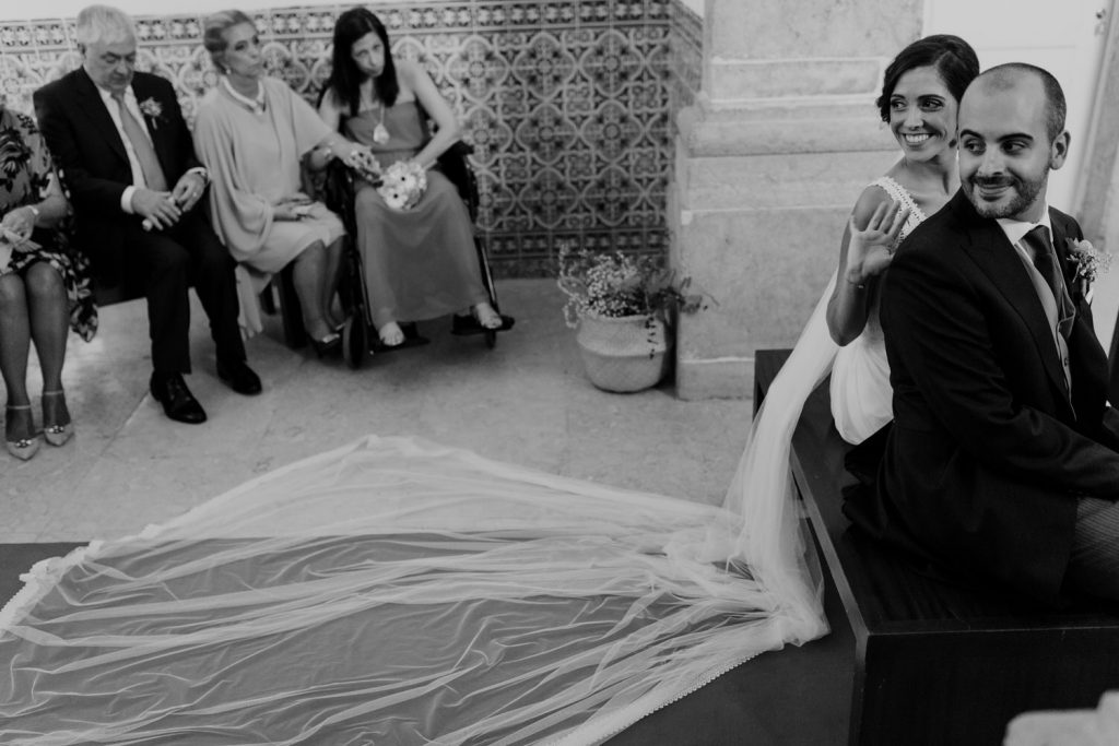 noivos sorriem para convidados do casamento durante a cerimónia religiosa