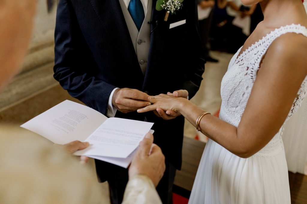 noivo coloca a aliança no dedo da noiva