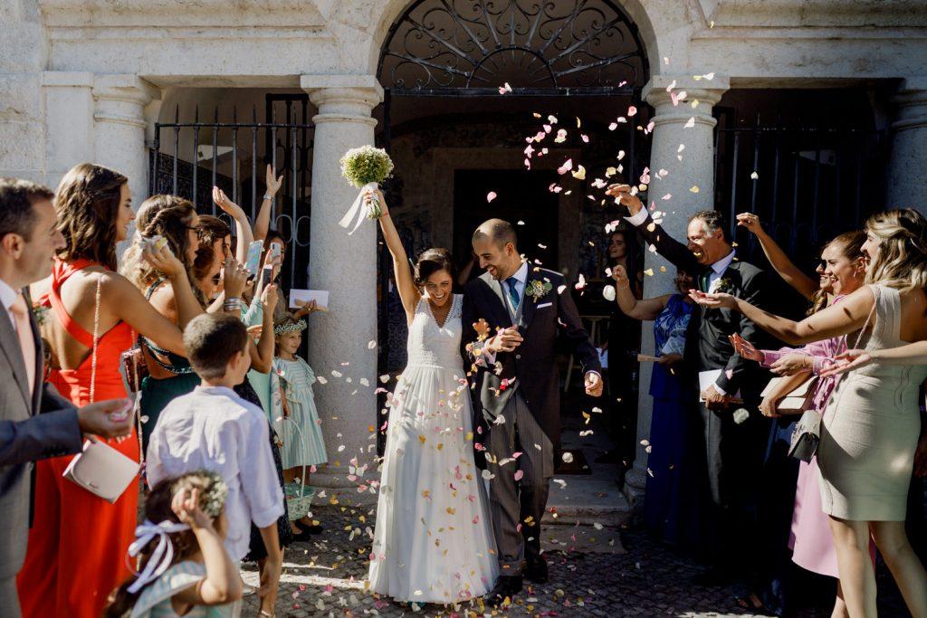 saida dos noivos do convento dos capuchos enquanto convidados lançam petalas de rosa