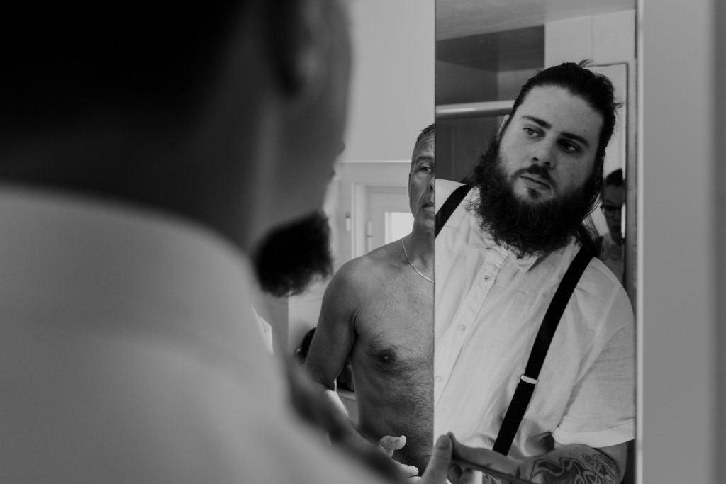 groomsman looks at the mirror
