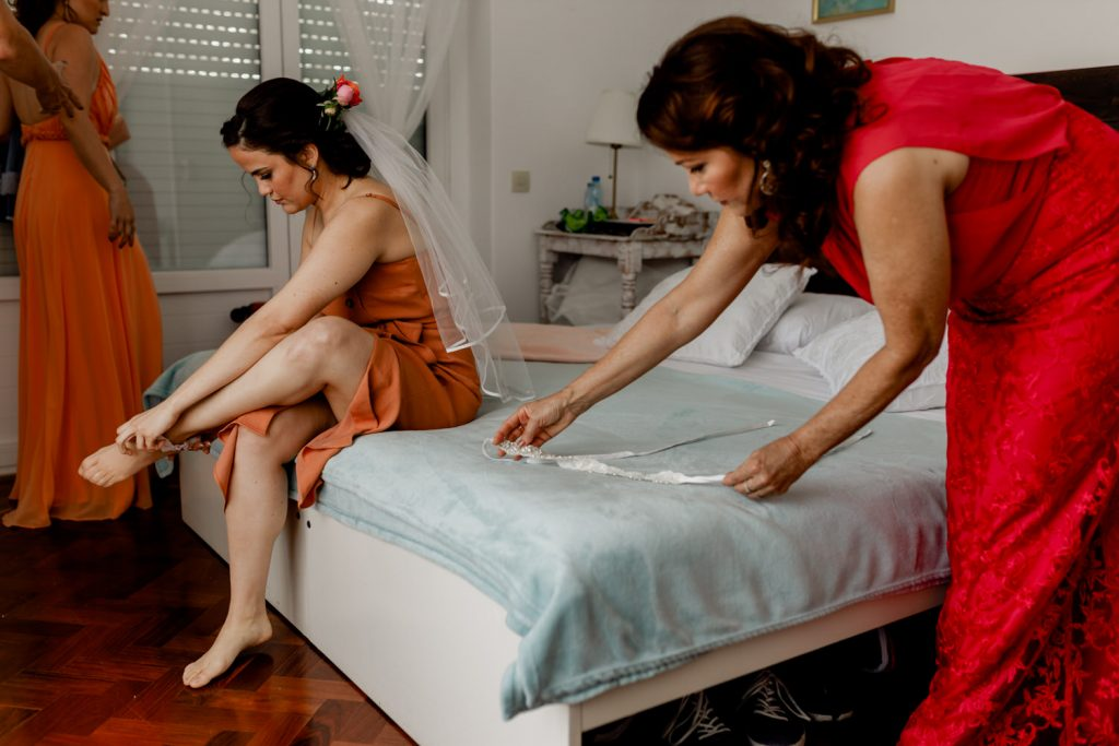 bride is getting ready for the wedding with the help of her mom