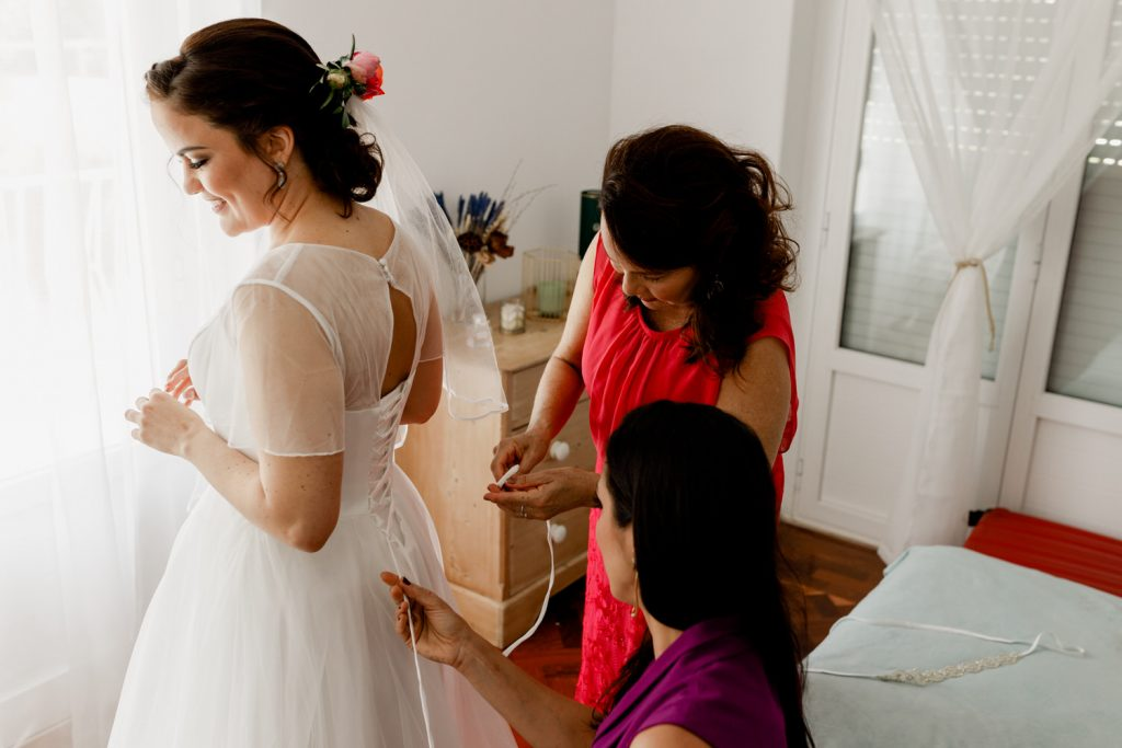 a noiva está a vestir o vestido de casamento