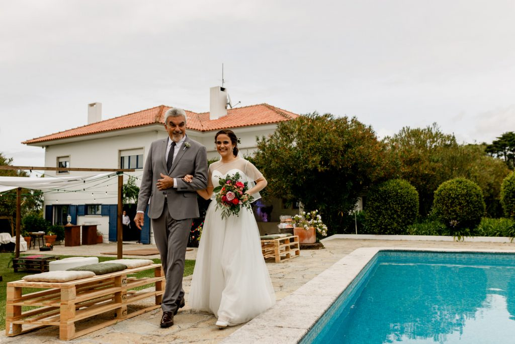 noiva caminha para o começo da cerimónia de casamento perto da piscina da quinta casa portuguesa
