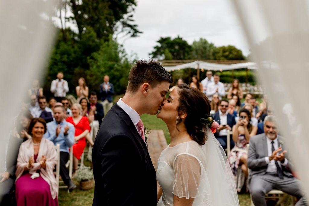 noivos dão um beijo no final da cerimónia de casamento