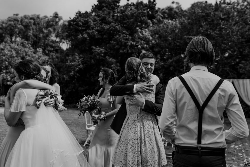 bride and groom hug their wedding guests after the wedding