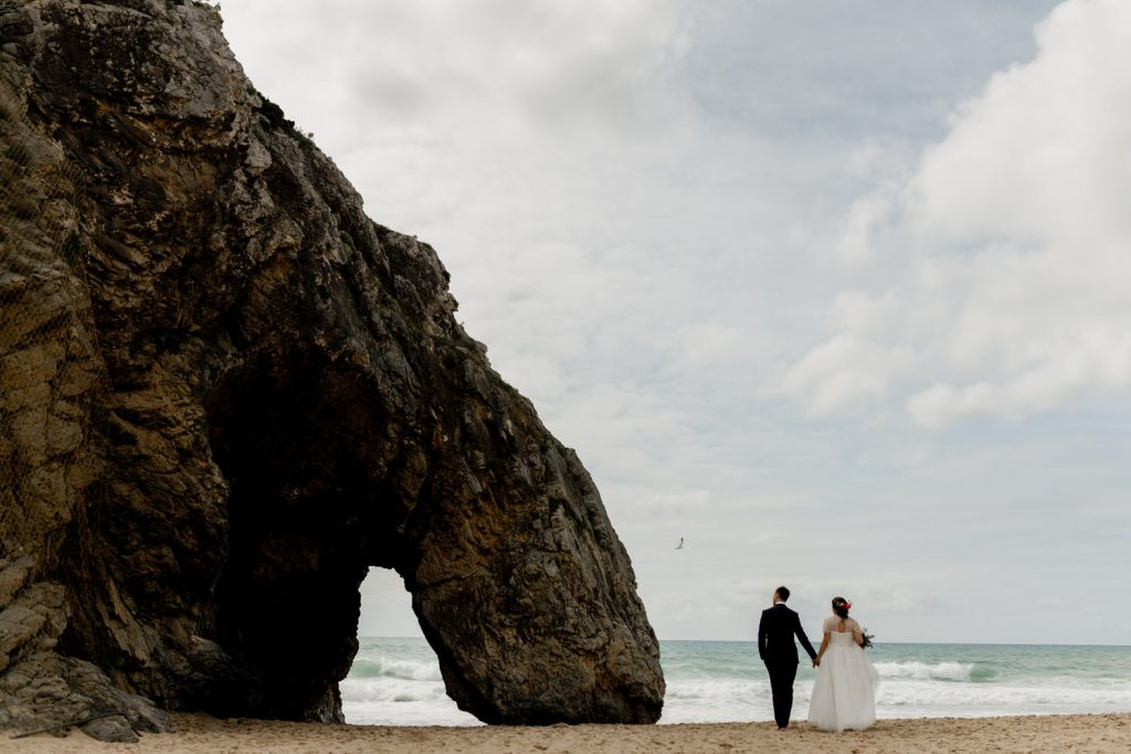 bride and groom walk on the Praia da Agrada beach