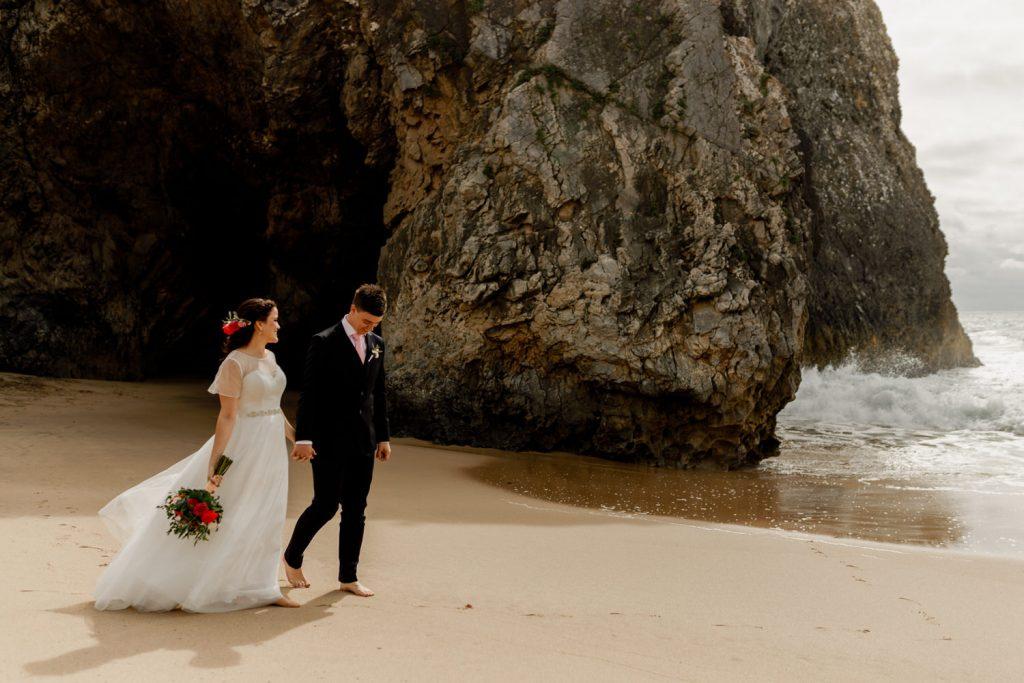 noivos passeiam pela praia da adraga em sintra