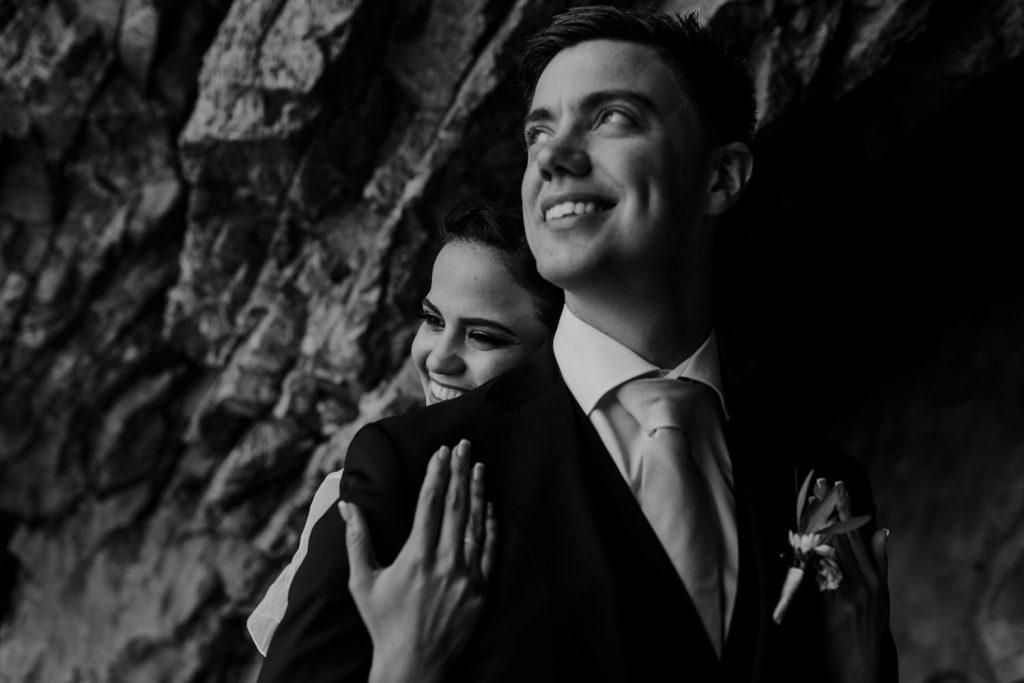 noivos abraçados a sorrir entre a rocha da praia da adraga