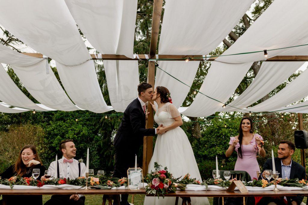 noivos dão beijo em cima das cadeiras durante o almoço