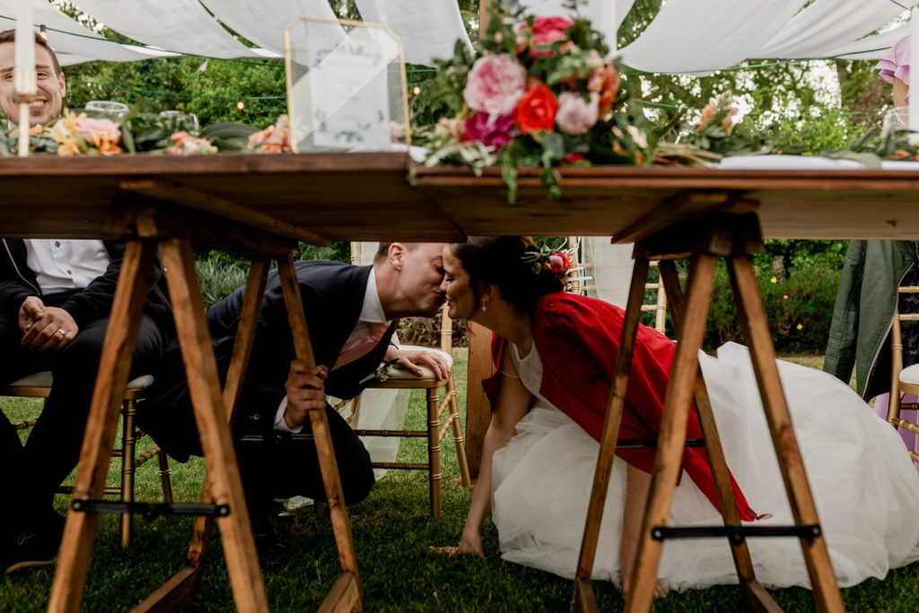bride and groom kiss under the table