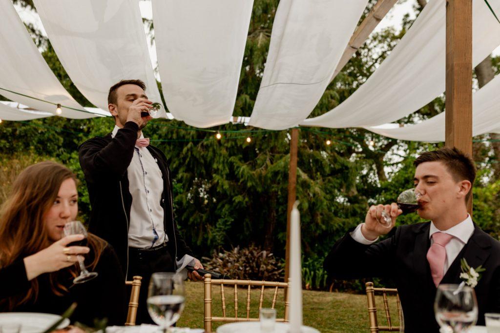 noivo e o seu irmão bebem vinho durante o casamento